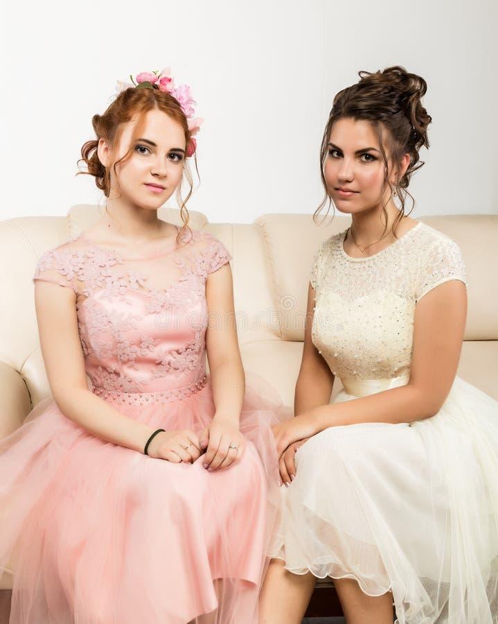 庄重装束的两个迷人的少妇坐沙发,嫩历史 免版税图库摄影