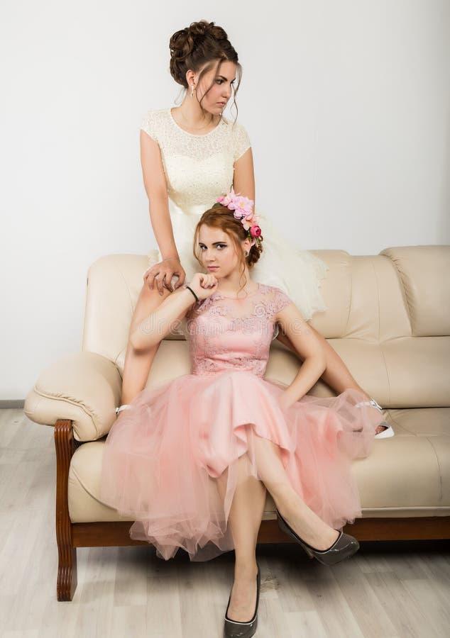 庄重装束的两个迷人的少妇坐沙发,嫩历史 图库摄影