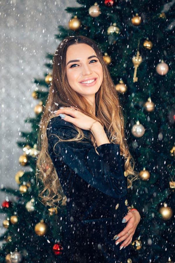 庄重装束的愉快的微笑的年轻女人在圣诞节内部背景 白雪公主 图库摄影
