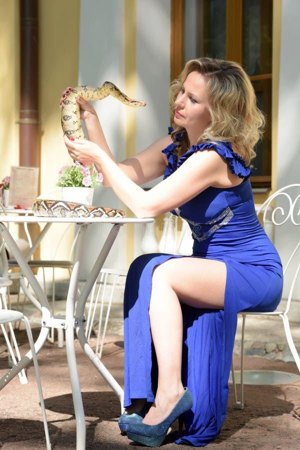 庄重装束的白肤金发的妇女与Python 免版税库存图片