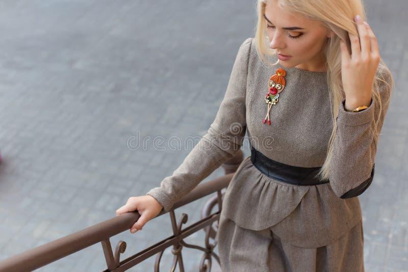 庄重装束的美丽的典雅的亭亭玉立的白肤金发的女孩与台阶的别针在城市 免版税库存照片