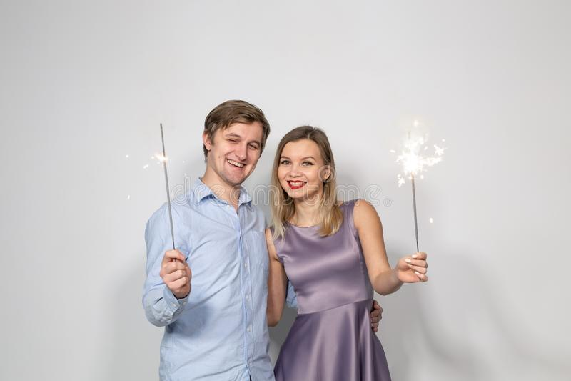 庆祝、党和假日概念-愉快的拥抱在与闪烁发光物的灰色背景的男人和妇女 图库摄影