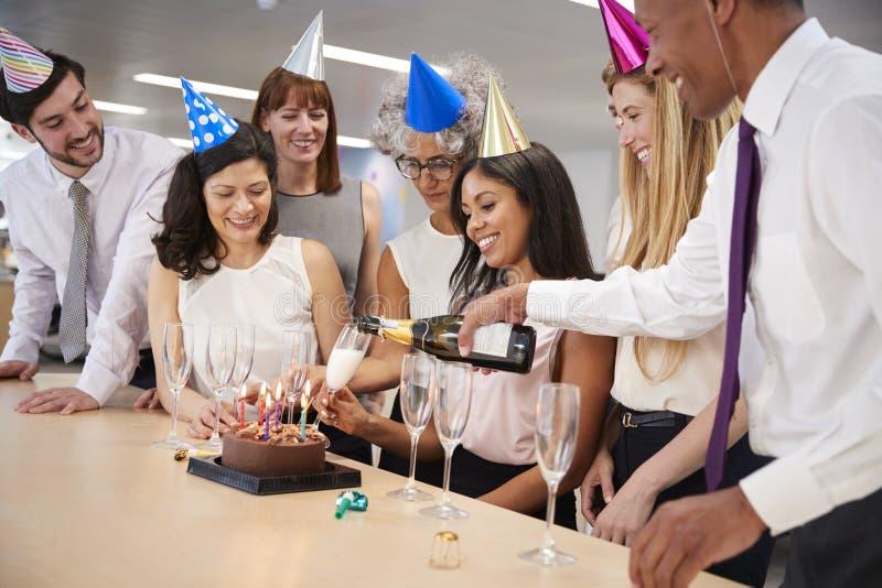 庆祝一个生日的同事在办公室倒香槟 免版税库存照片