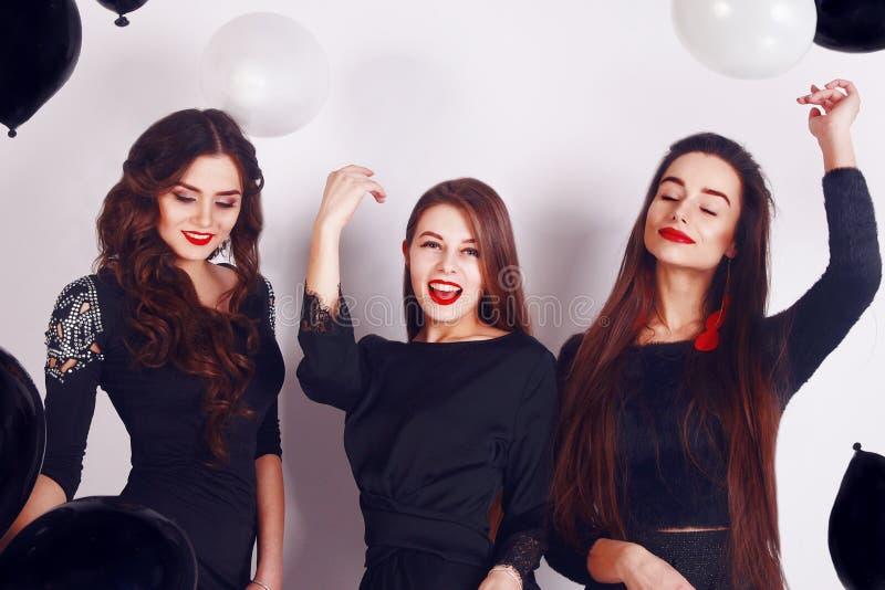 庆祝三名美丽的时髦的妇女的疯狂的党时间典雅的晚上偶然黑礼服的,获得乐趣,跳舞 图库摄影