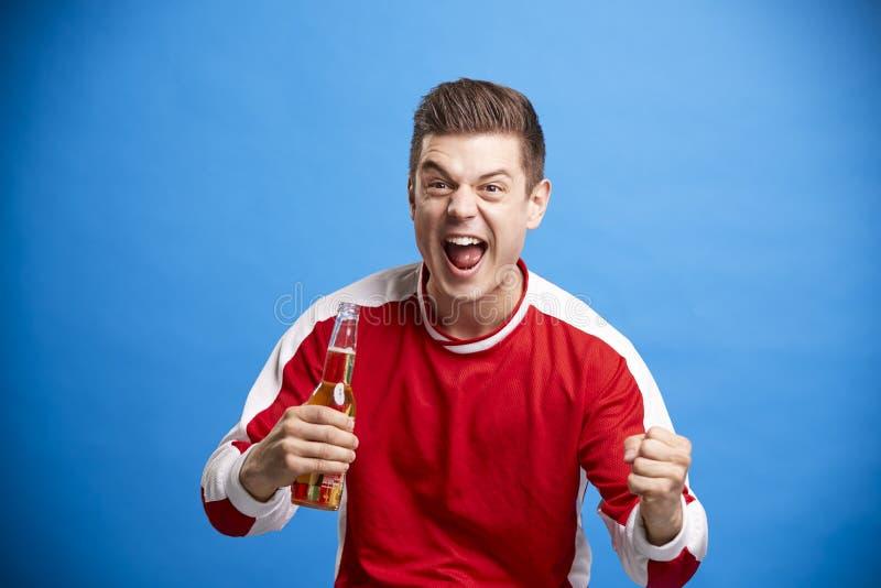 庆祝与一个瓶的年轻人男性体育迷啤酒 图库摄影