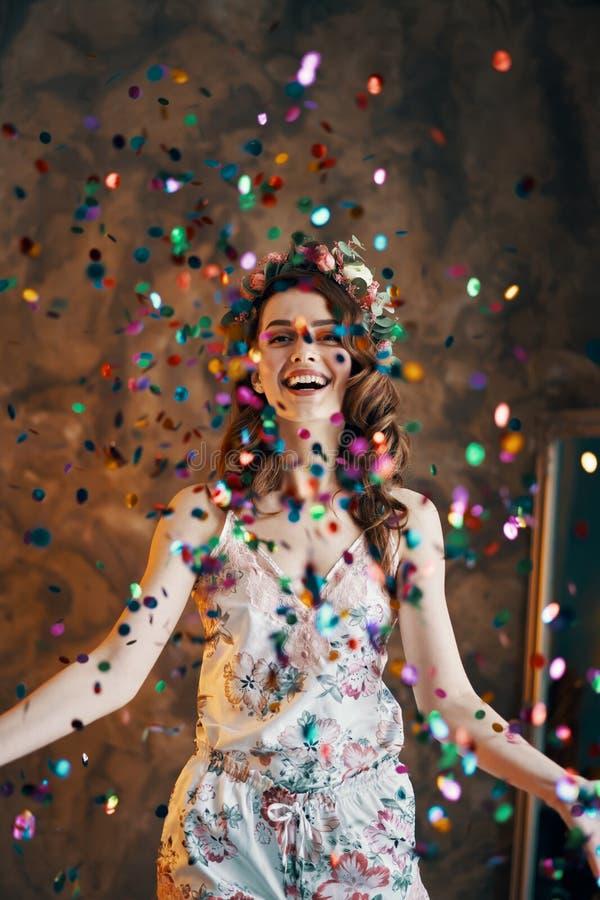 庆祝与五彩纸屑的愉快的美女落到处在室 免版税库存照片
