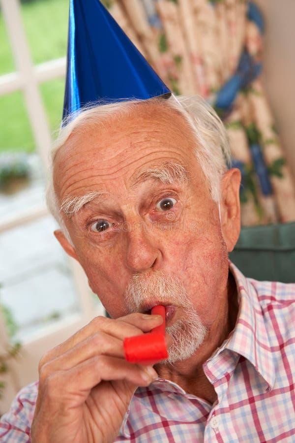 庆祝与党帽子和吹风机的老人 免版税库存照片