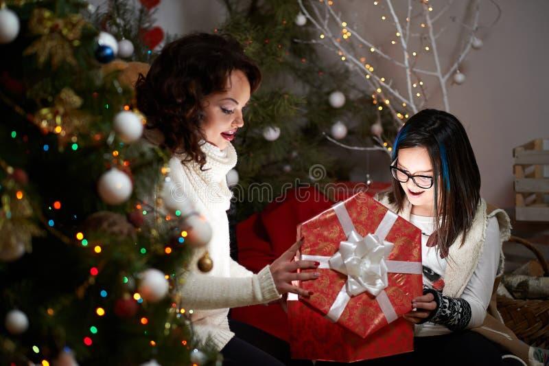 庆祝与她的母亲的快乐的女孩圣诞节在hom 免版税库存照片