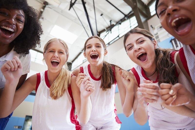庆祝与教练的女性高中蓝球队画象  库存图片