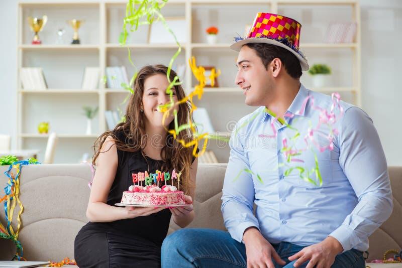 庆祝与蛋糕的年轻夫妇生日 免版税库存照片