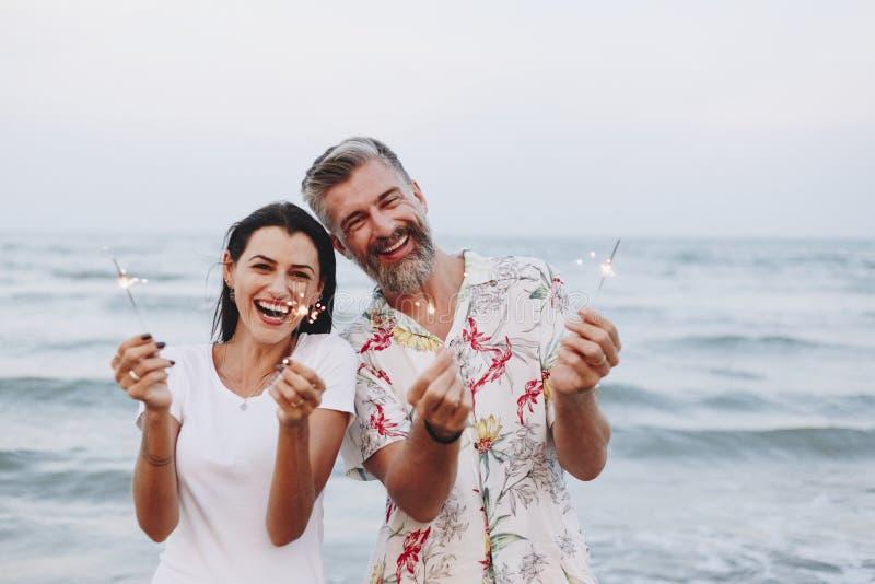 庆祝与闪闪发光的夫妇在海滩 免版税库存照片