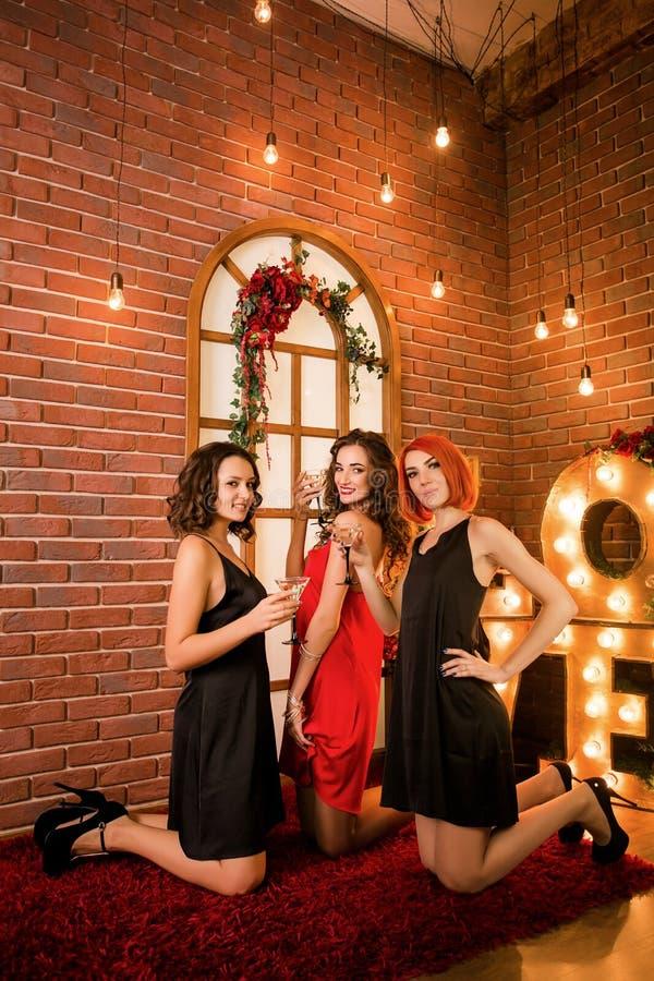 庆祝他们的生日的三个女孩 在相同礼服、黑色和红色的妇女的聚会 库存图片