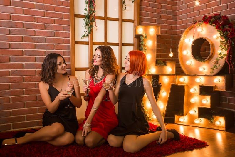 庆祝他们的生日的三个女孩 在相同礼服、黑色和红色的妇女的聚会 免版税库存图片