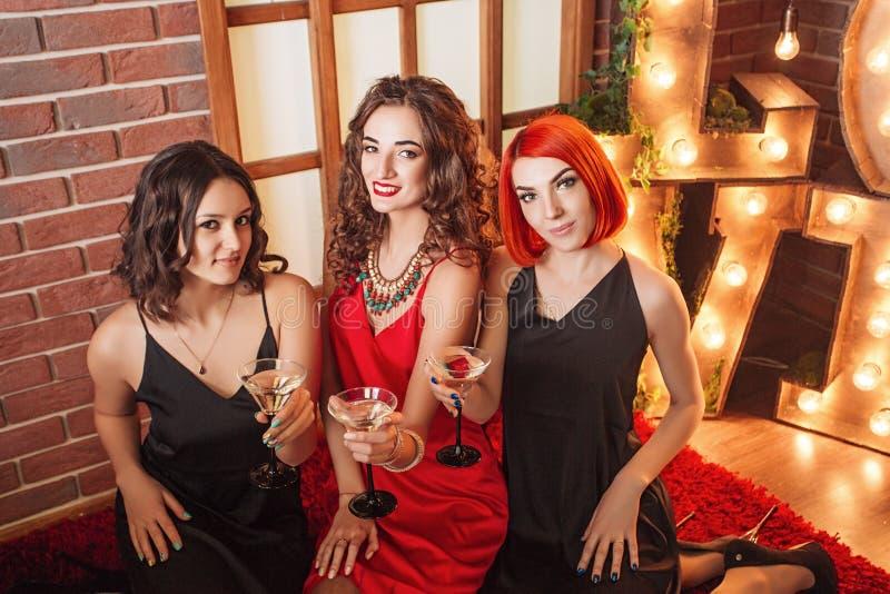 庆祝他们的生日的三个女孩 在相同礼服、黑色和红色的妇女的聚会 库存照片