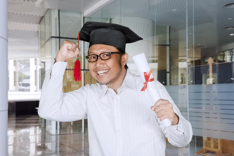 庆祝他的毕业的年轻人 免版税库存图片