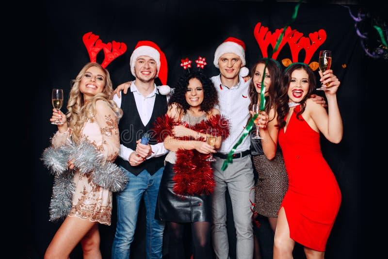 庆祝圣诞节或除夕党的朋友 戴香槟眼镜的青年人在圣诞晚会的 免版税库存照片