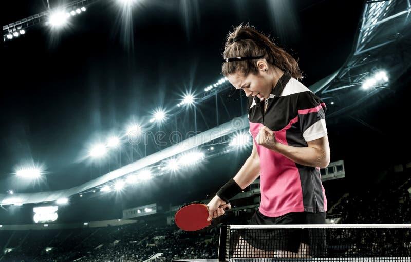 庆祝在乒乓球的年轻英俊的妇女至善至美的胜利 库存图片