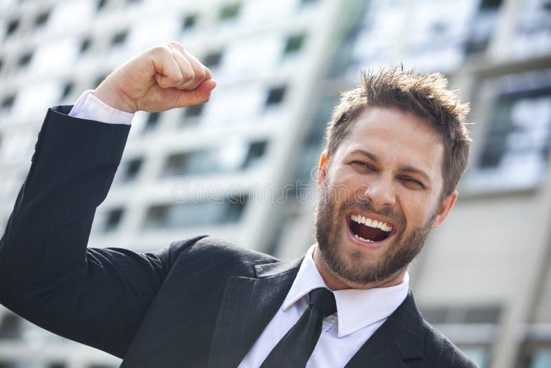 庆祝在城市的年轻成功的商人 免版税库存图片