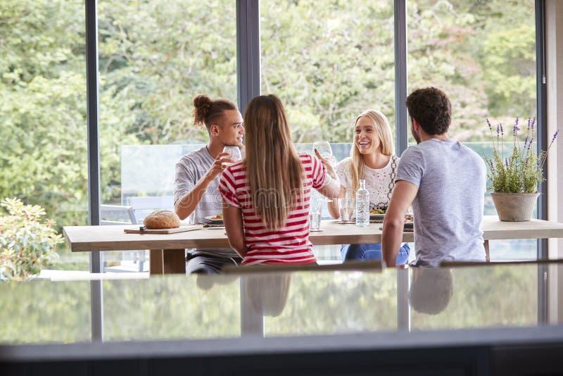 庆祝在晚餐会的多族群四个年轻成人朋友培养他们的酒杯,看见从厨房 免版税库存照片