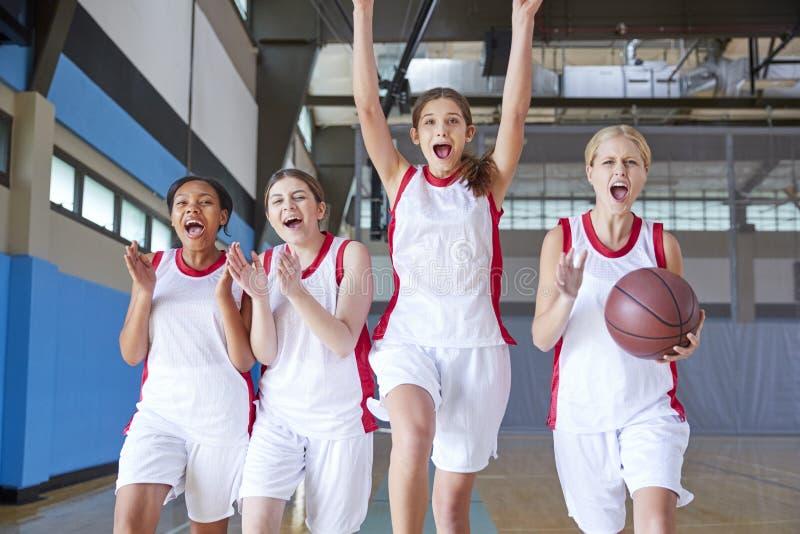 庆祝在法院的女性高中蓝球队画象  免版税库存照片