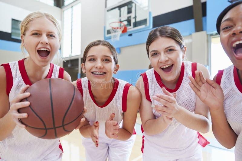 庆祝在法院的女性高中蓝球队画象  免版税库存图片