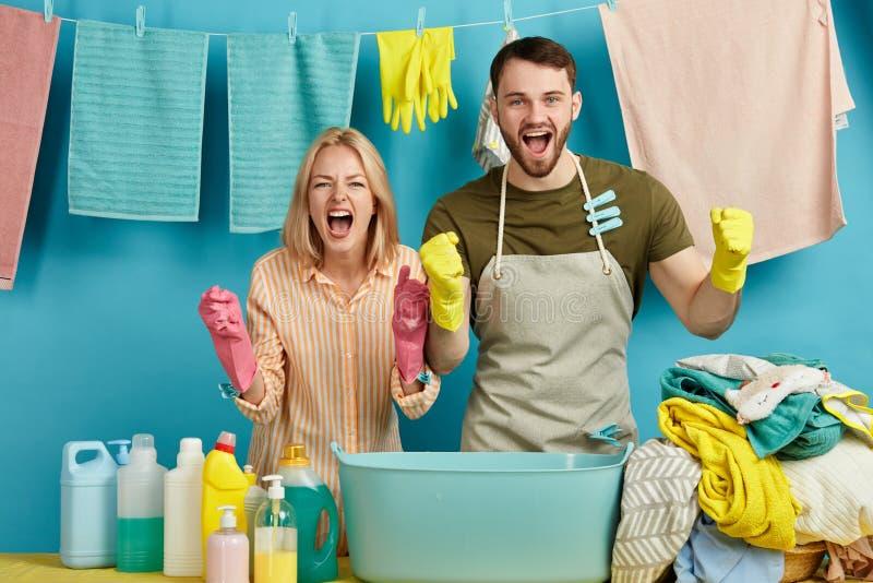 庆祝在洗衣店的情感年轻夫妇胜利 库存照片