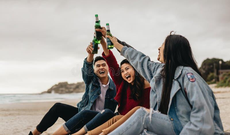 庆祝在海滩的亚裔朋友 免版税库存照片