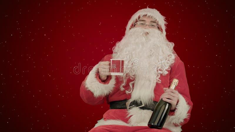 庆祝在红色背景的圣诞老人香槟与雪 库存照片