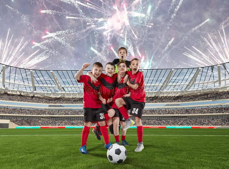 庆祝在足球场的五位少年足球运动员胜利 库存照片