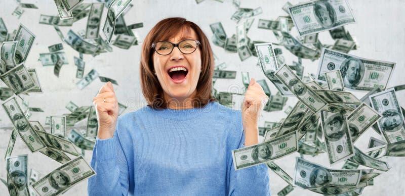 庆祝在金钱的愉快的资深妇女成功 库存照片