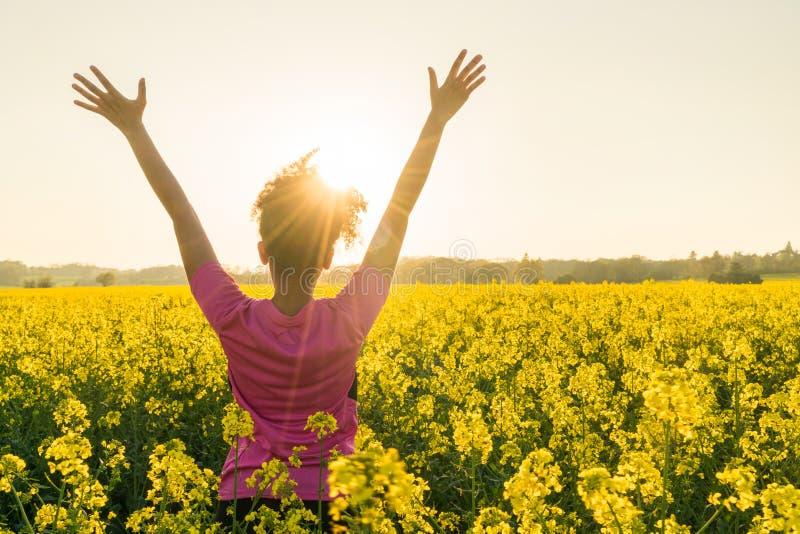 庆祝在黄色花的女性女子运动员赛跑者 免版税库存照片