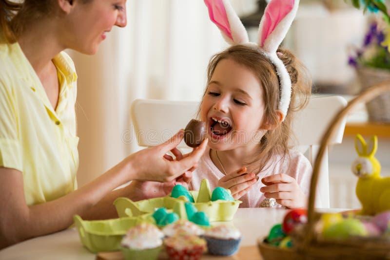 庆祝复活节的母亲和女儿,吃朱古力蛋 免版税库存照片