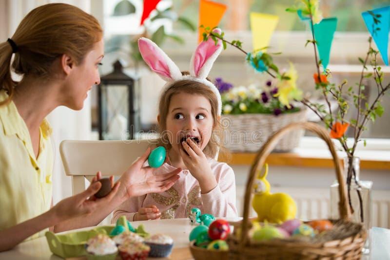 庆祝复活节的母亲和女儿,吃朱古力蛋 免版税图库摄影