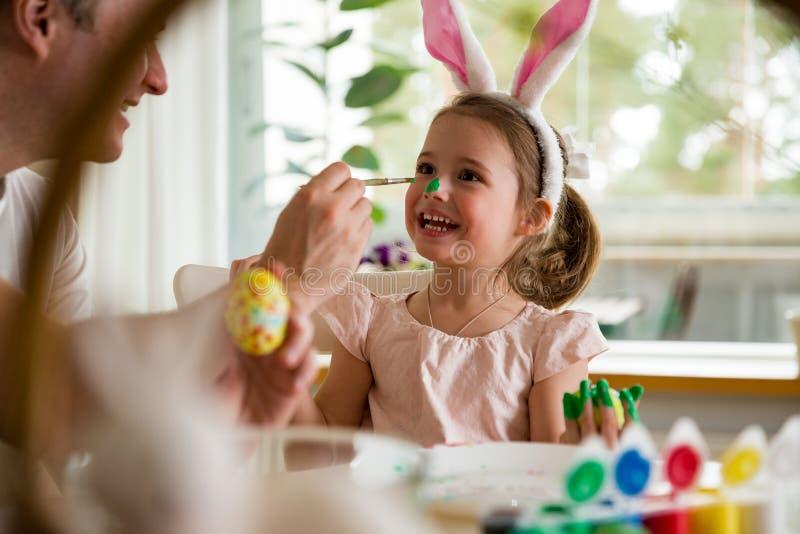 庆祝复活节,与刷子的绘的鸡蛋的父亲和女儿 免版税库存照片