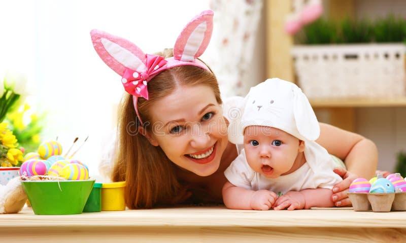庆祝复活节母亲和婴孩有兔宝宝耳朵的愉快的家庭 免版税库存图片