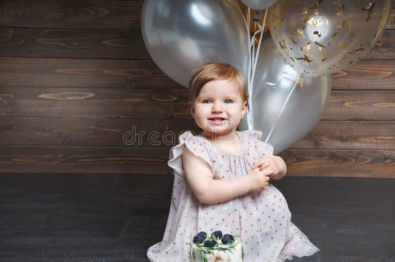 庆祝她的与蛋糕和气球的逗人喜爱的可爱的女婴画象第一个生日 免版税库存图片
