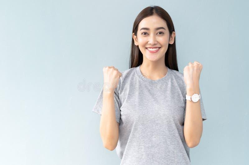 庆祝她的成功的愉快的年轻亚裔女孩,在拳头和看保留手被握紧在灰色的照相机 免版税库存图片