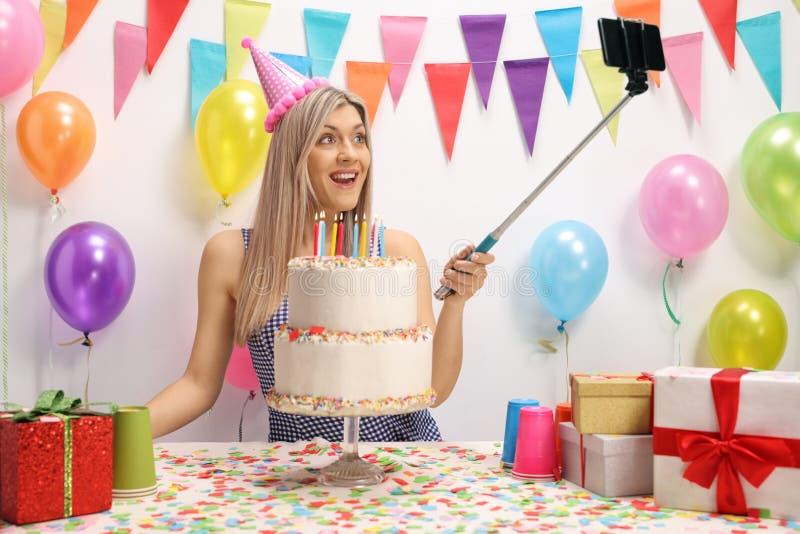 庆祝她的生日和采取selfie的少妇 免版税图库摄影