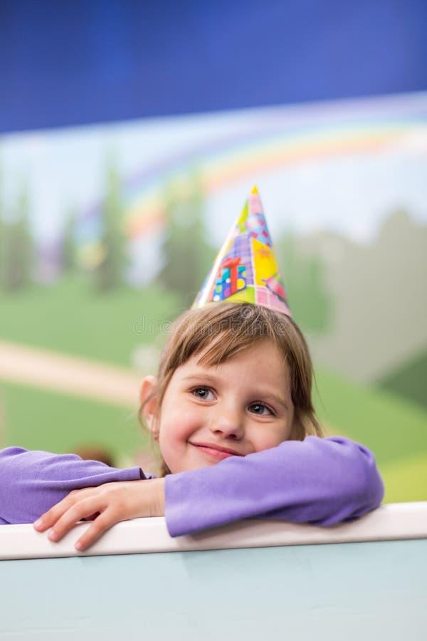 庆祝她的生日的小女婴 帽子和欢乐心情 库存照片
