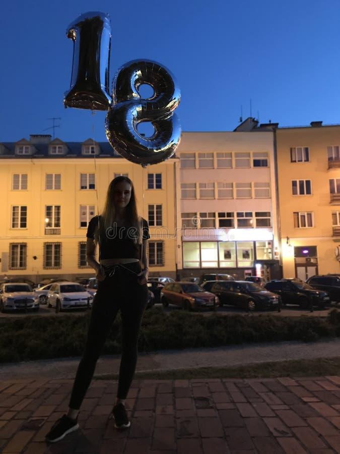 庆祝她的18生日的女孩,站立与气球 免版税库存照片