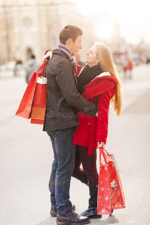 庆祝情人节的年轻夫妇拿着购物带来 库存图片