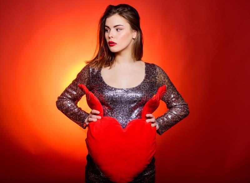 庆祝情人节 女孩构成和性感的低颈露肩的礼服 妇女有吸引力的时装模特儿举行心脏玩具 免版税库存图片