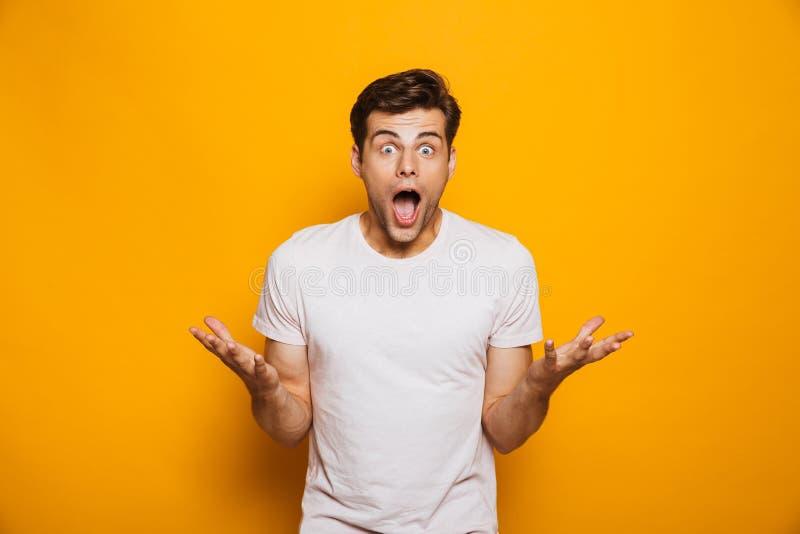 庆祝成功的一个兴奋的年轻人的画象 免版税库存图片