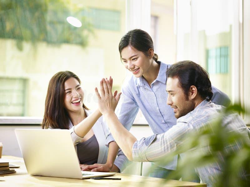 庆祝成功的亚裔商人在办公室 免版税图库摄影