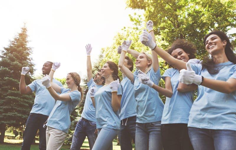 庆祝成功的小组愉快的志愿者在公园 免版税库存图片