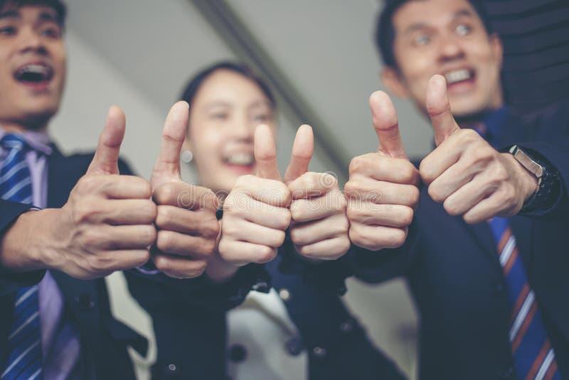 庆祝成功的微笑的愉快的商人和女实业家 免版税库存图片