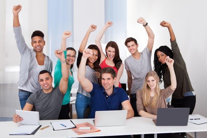 庆祝成功的愉快的大学生在教室 库存照片