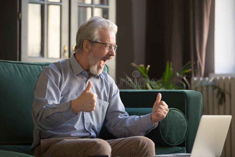 庆祝成功的愉快的激动的灰发的成熟人,使用膝上型计算机 库存图片