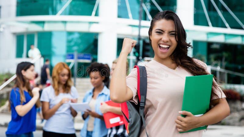 庆祝成功的检查的拉丁美洲的女学生 免版税库存照片