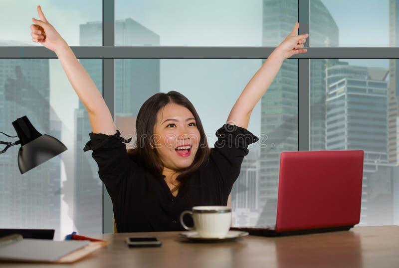 庆祝成功的美丽的亚裔日本女实业家激发举胳膊作为工作在窗口书桌上的优胜者在中央busine 免版税库存照片
